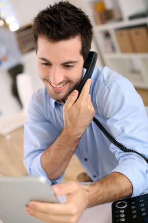 Talking on the phone: Cheerful man in office answering the phone