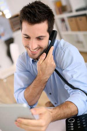 hablando por celular: Hombre alegre en la oficina que contesta el tel?fono
