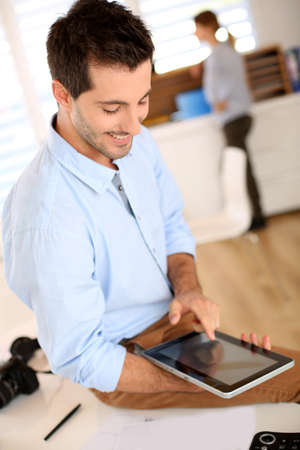 Trendy guy working in office with tablet photo
