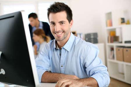 desktop background: Man in office working on desktop computer