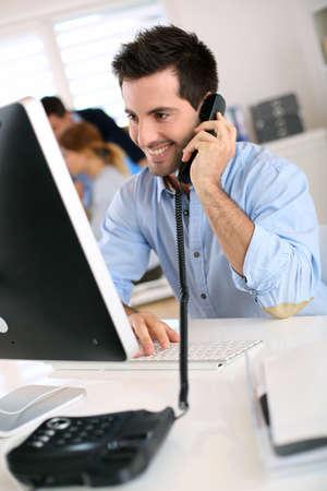 amigas conversando: Sonriente trabajador de oficina hablando por teléfono