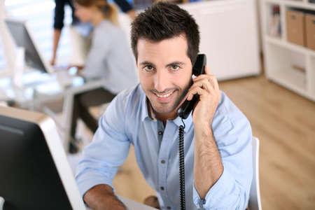obreros trabajando: Sonriente trabajador de oficina hablando por tel?fono Foto de archivo