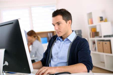 Man working in office in front of desktop computer photo