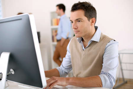 computer training: Man working in office in front of desktop computer