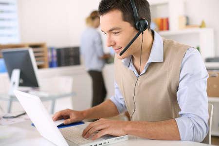 recepcionista: Retrato de consultor en el tel�fono con un aud�fono
