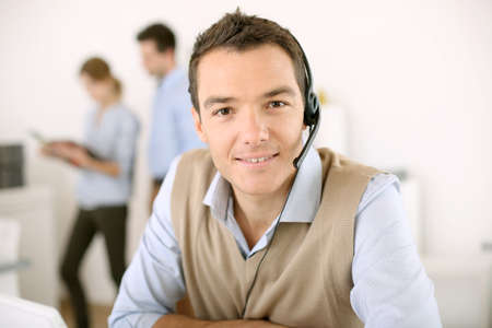 Portrait of consultant on the phone with headset Stock Photo