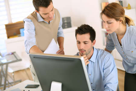 startup: Workteam in office working on desktop computer Stock Photo