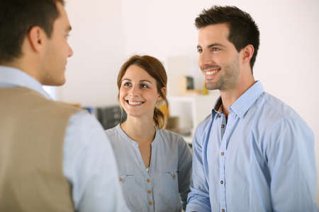 Cheerful couple shaking hand to salesman photo