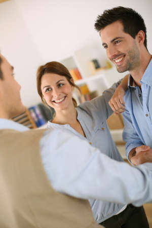Cheerful couple shaking hand to salesman photo