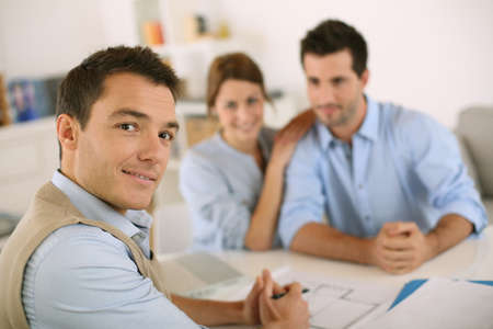 Smiling financial adviser with young couple photo