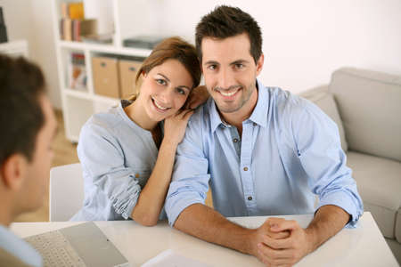 financial guidance: Smiling couple in real-estate agency
