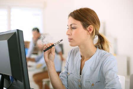 cigarrillos: Chica de fumar con el cigarrillo electr�nico en la oficina