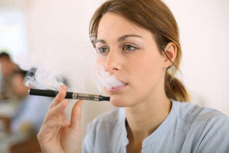 Portrait of woman smoking with electronic cigarette photo