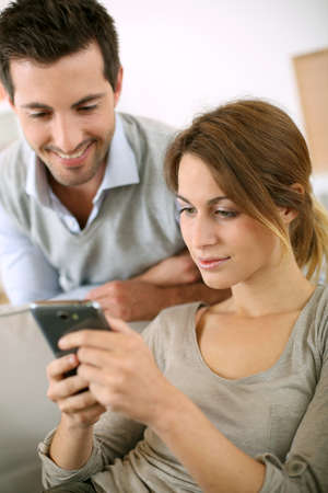 couple on couch: Young people at home using smartphone
