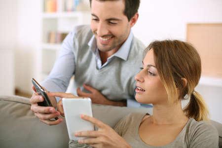 Jong koppel met behulp van smartphone thuis