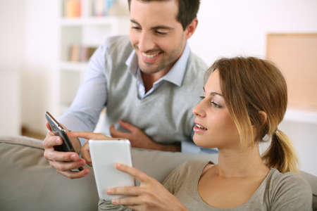 man phone: Young couple using smartphone at home