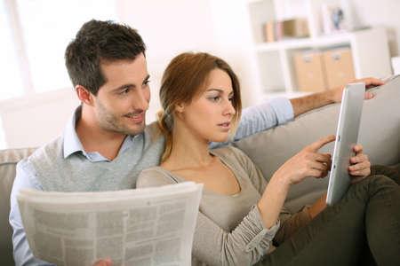 mann couch: Couple Lesen von Nachrichten sowohl auf Presse und Internet