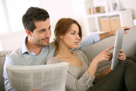 reading news: Couple reading news on both press and internet Stock Photo
