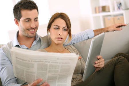 pda: Couple reading news on both press and internet Stock Photo