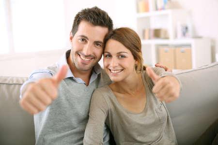 pareja en casa: Pareja joven que muestra los pulgares para arriba