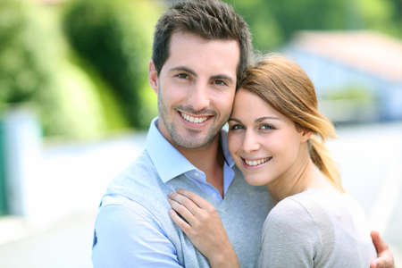 Cheerful couple standing in front of new house photo