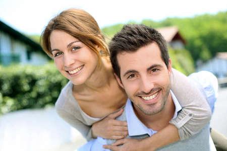 pareja abrazada: Pareja alegre de pie delante de la nueva casa
