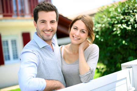 pareja abrazada: Alegre joven de pie delante de la nueva casa