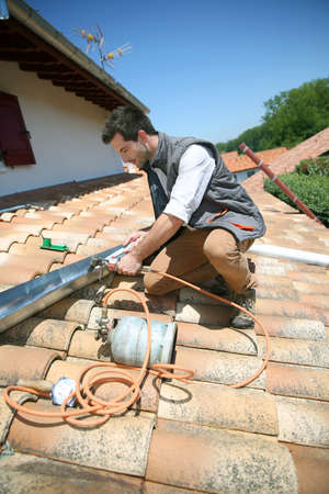 Roofer working on house roof to fix gutter photo