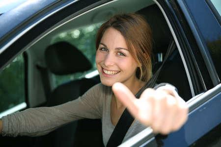 cinturon seguridad: Muchacha alegre sentado en coche con el pulgar arriba Foto de archivo