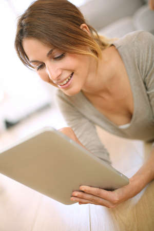 Smiling girl websurfing on internet with tablet photo