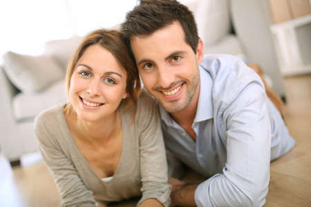 Cheerful couple laying on the floor at home photo