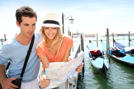 Tourists looking at map in front of San Giorgio Maggiore Island, Venice photo