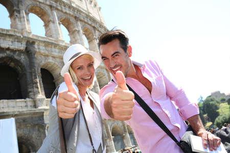コロッセオの前で親指を現してカップル