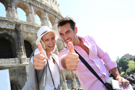 tourist: Couple showing thumbs up in front of the Coliseum Stock Photo