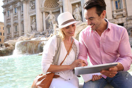 Couple in Rome using pad by the Trevi Fountain Stock Photo