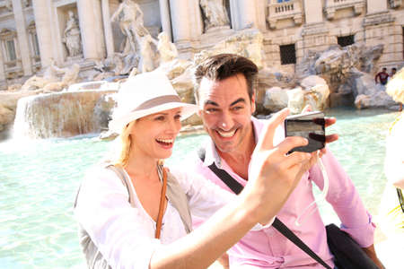 Couple taking picture in front of the Trevi Fountain Фото со стока