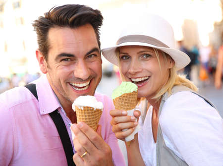 Cheerful couple in Rome eating ice cream cones photo