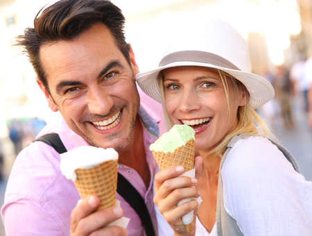 eating in: Cheerful couple in Rome eating ice cream cones