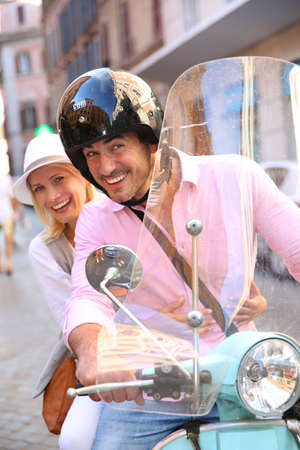Cheerful couple in Rome riding scooter photo