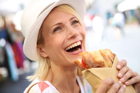 eating in: Cheerful blond girl in Rome eating Focaccia sandwich