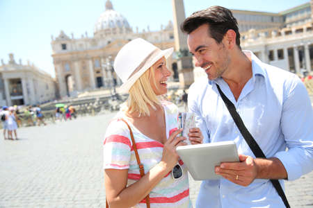 Couple of tourists using digital tablet in Rome