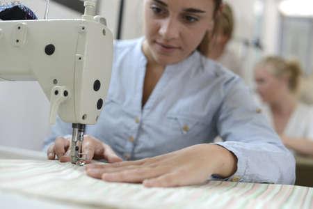 Muchacha del estudiante en la clase de entrenamiento de trabajo en la m�quina de coser photo