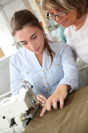 dressmaking: Woman in dressmaking class helping student