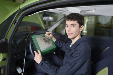 Students doing car diagnostic with computer photo