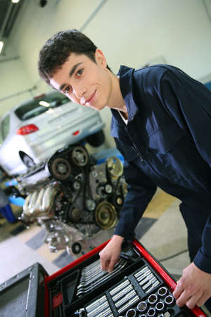 Student in mechanics working on car engine photo