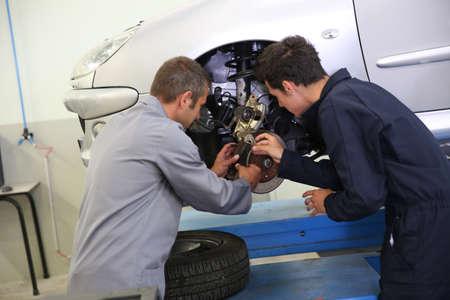 mecanico: Instructor mostrando estudiante c�mo cambiar los frenos del coche Foto de archivo