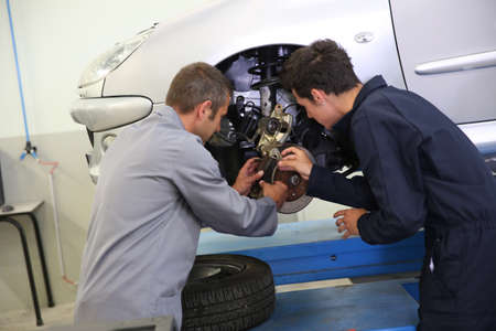 car mechanic: Instructor showing student how to change car brakes