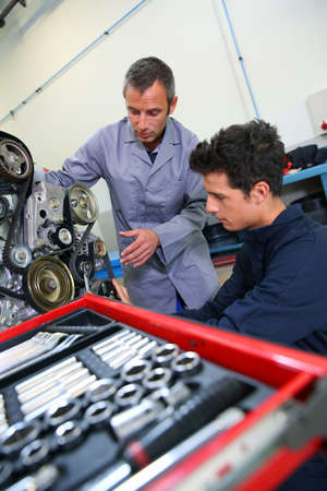 Professional trainer teaching student how to fix car engine photo