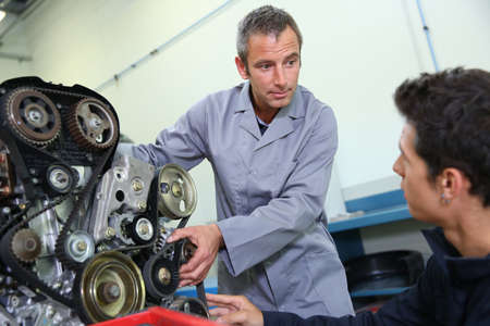 Professional trainer teaching student how to fix car engine Stock Photo - 20690786