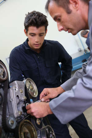 Professional trainer teaching student how to fix car engine Stock Photo - 20684901